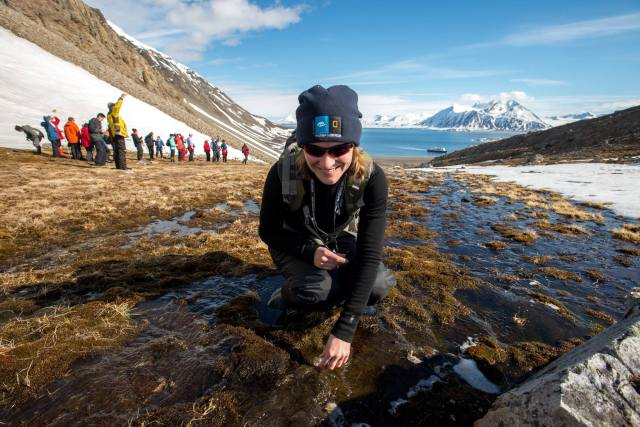 Photo credit to Eric Guth, collecting water from a snowmelt stream in Arctic Svalbard